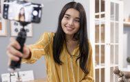 Influencer mulher jovem segura um celular em posição de selfie